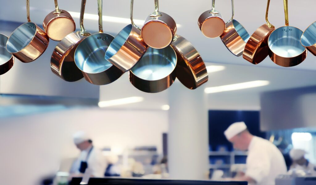 Copper pots hanging in the foreground of a restaurant kitchen, as chefs work in the background