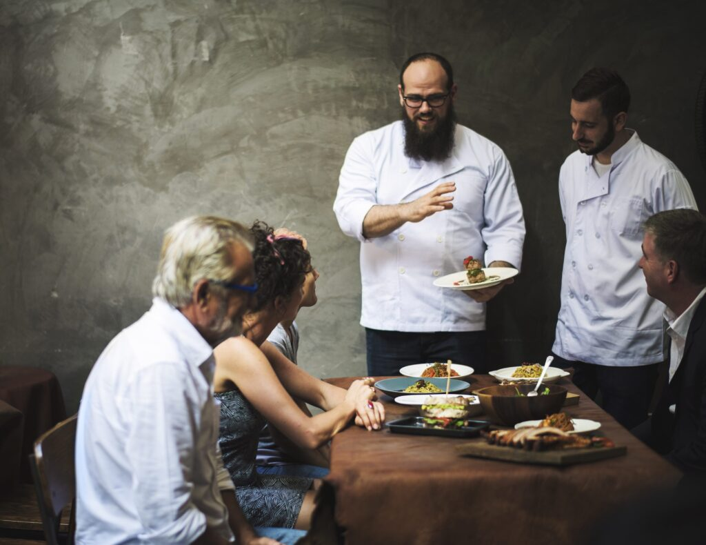 Two chefs explain the concept of a dish to diners seated in his restaurant