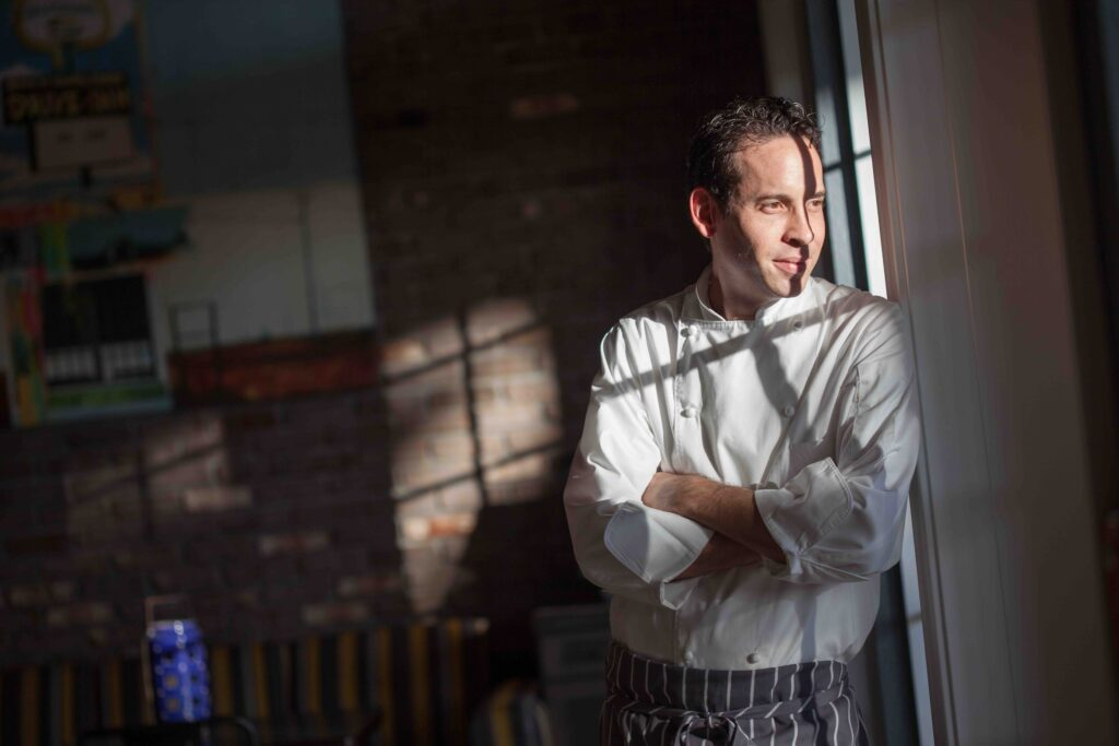 A male chef in uniform in a dark room staring out of the window