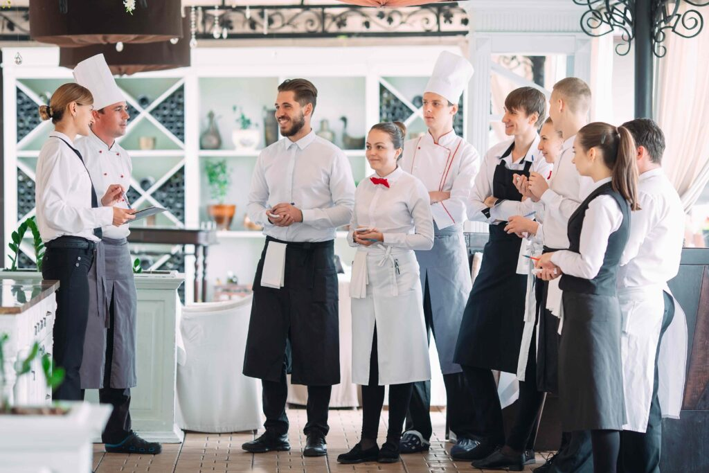 A restaurant manager briefs her front of house and back of house staff before service