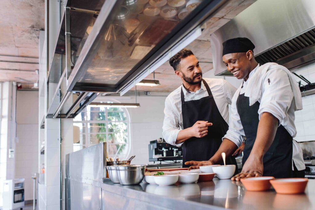 Two chefs chat as they work in a restaurant kitchen