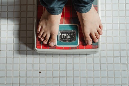 Two feet on a weighing scale on a tiled floor