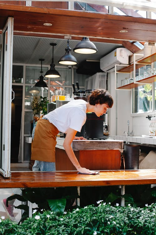 A female chef in a cafe cleaning a table