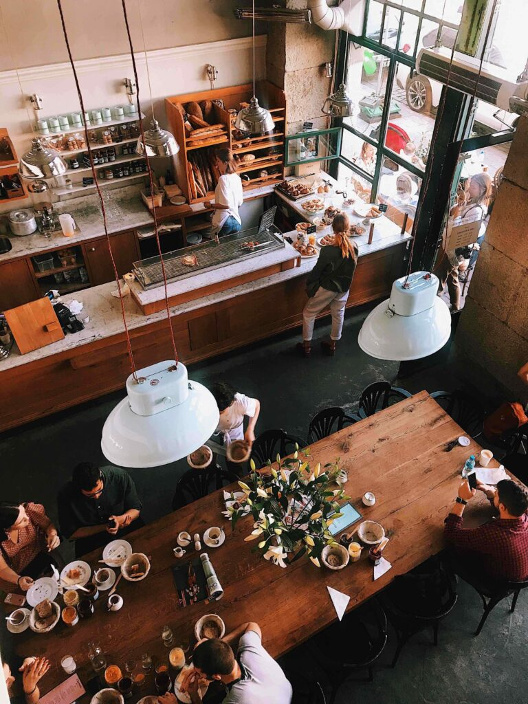 A bird's eye view of a cafe with seated customers at a table and a staff member serving a lady at the counter.