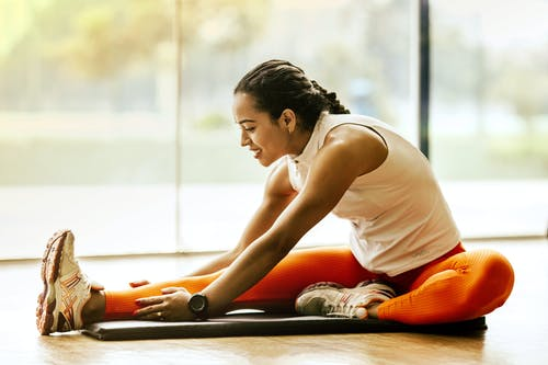 A woman stretching on a yoga mat.