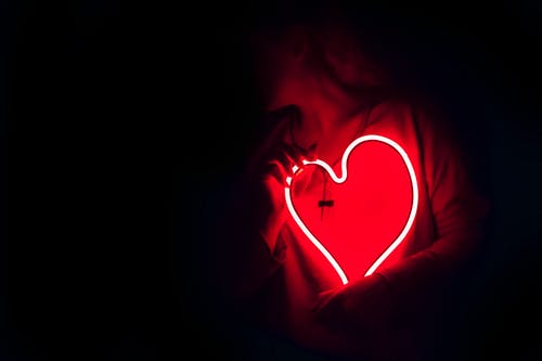 A lady carrying a neon red heart.