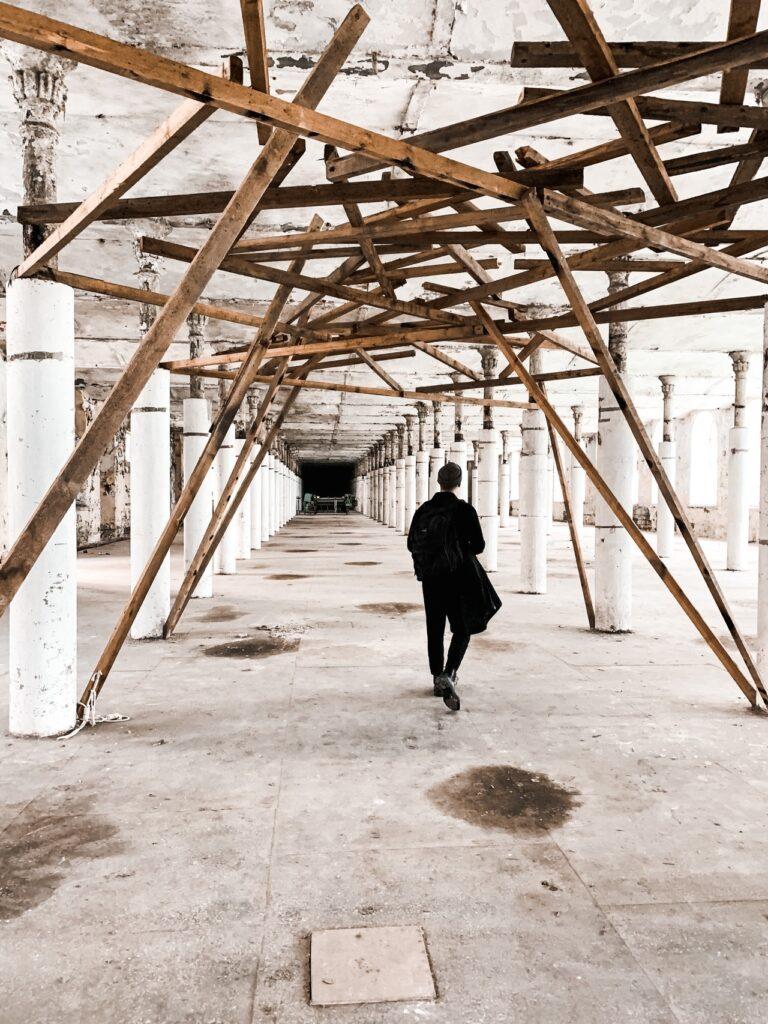 A man walking under scaffolding inside building