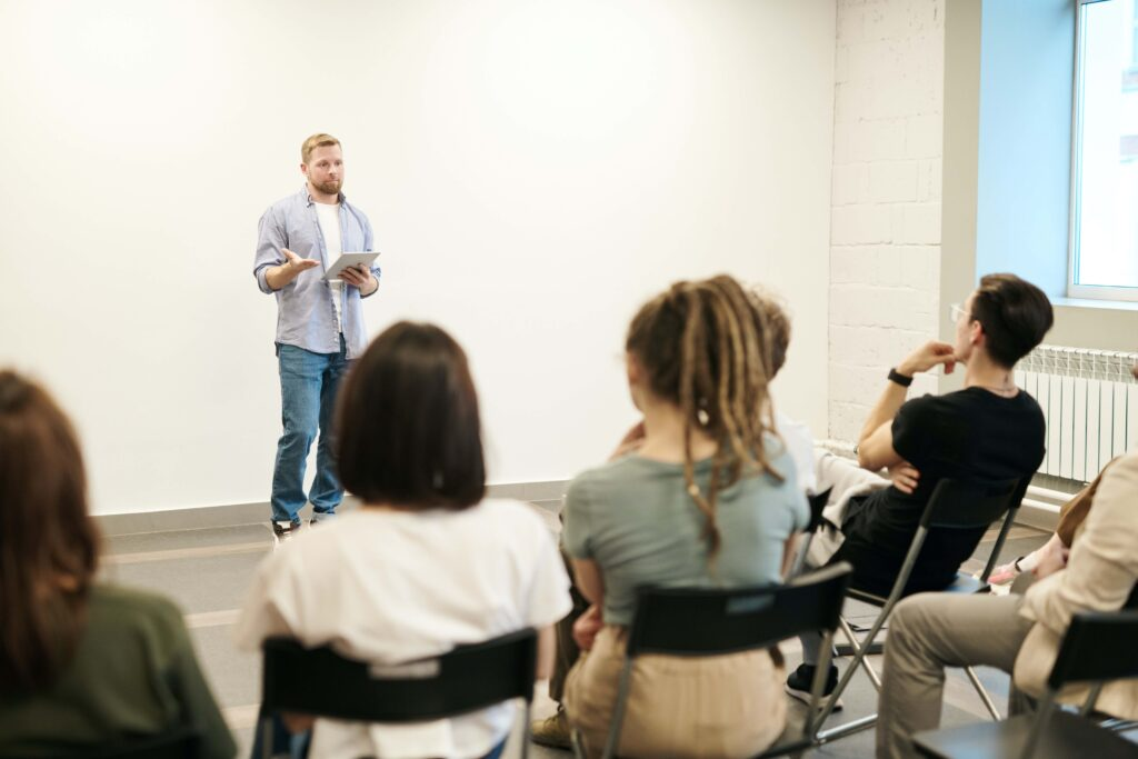 A man presenting in front of an audience  (click allow images)