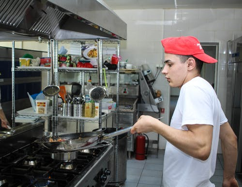 A young chef in a white t-shirt and red cap tossing ingredients in a frying pan he his holding up in the air.