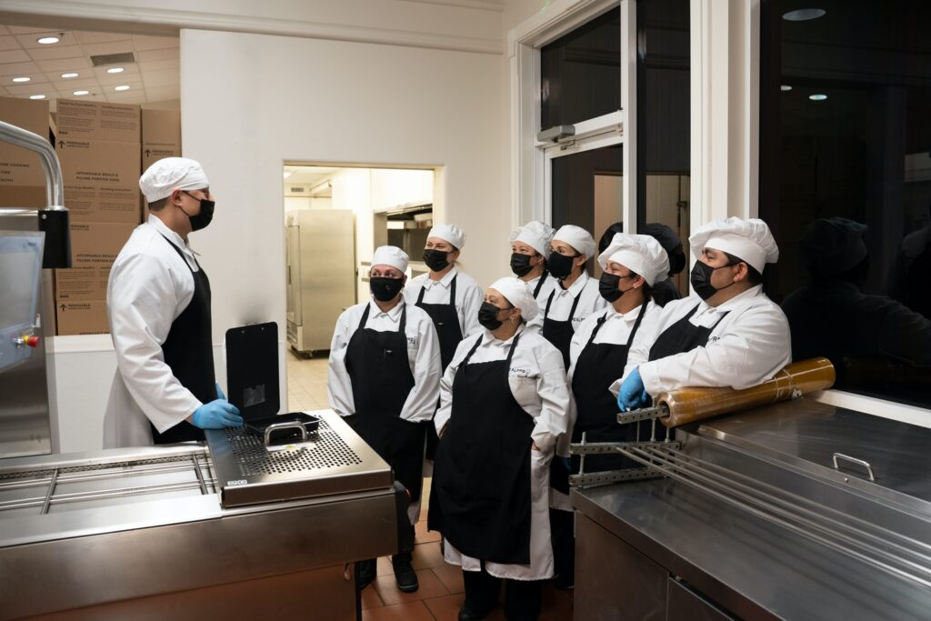A Head Chef talking to his team in the kitchen