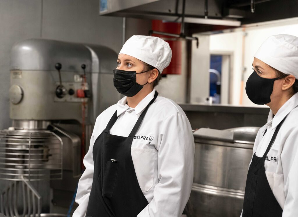 Two female chefs in the kitchen wearing masks.